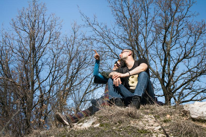 Couple Man and Woman sitting on cliff enjoying mountains and lan stock images
