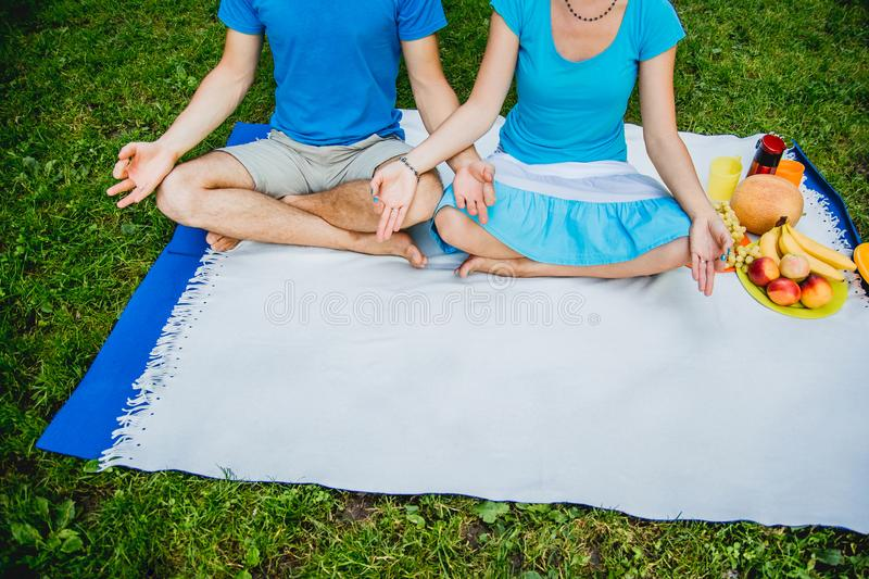 Couple man and woman sitting on the meadow with green grass in the Lotus position. Meditate in peace and freedom stock image