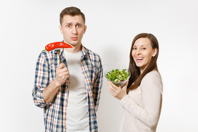 Couple, man, woman standing with green fresh salad in glass bowl, red hot chili pepper on fork isolated on white royalty free stock images