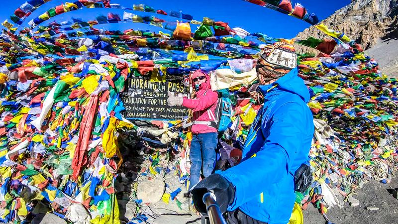Nepal - Couple at the Thorung La Pass. Couple, man and woman at the Thorung La Pass, Annapurna Circuit Trek, Nepal. Congratulations for the effort. Colorful royalty free stock images