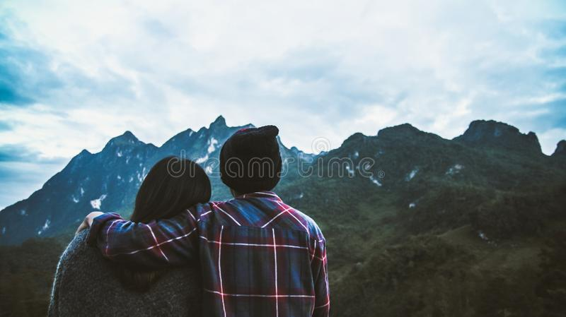 Couple man and woman tourist at top of mountain in Scottish shirt and black hat hiking at mountain peak above clouds and fog Hiker stock photography