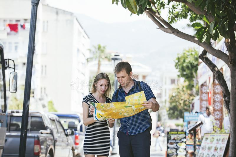 Couple man and woman walking around the city with map of romantic and happy royalty free stock images