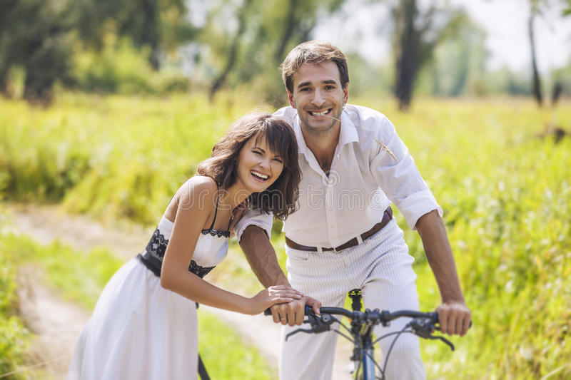 Couple man and woman in wedding style with bikes. Couple men and women in wedding style with bikes in nature happy royalty free stock photos