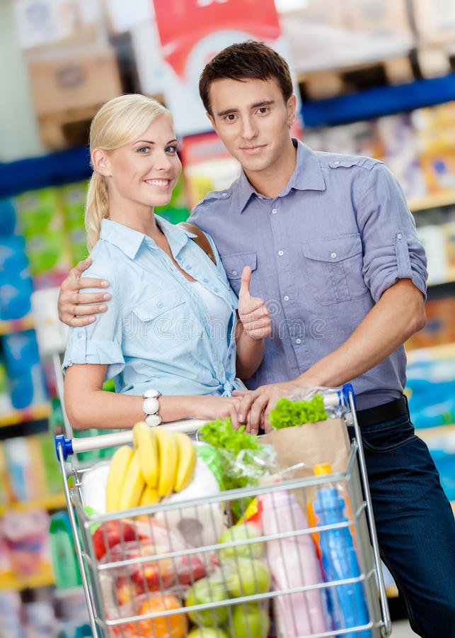 Couple in the market with cart full of food. Half-length portrait of couple in the market with cart full of food. Concept of consumerism and healthy food stock image