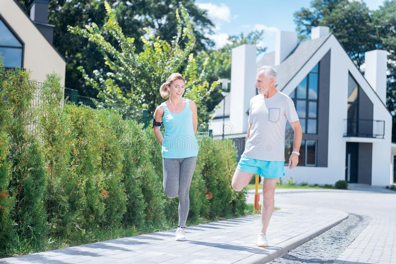 Couple of mature businessmen stretching together after long morning run stock images