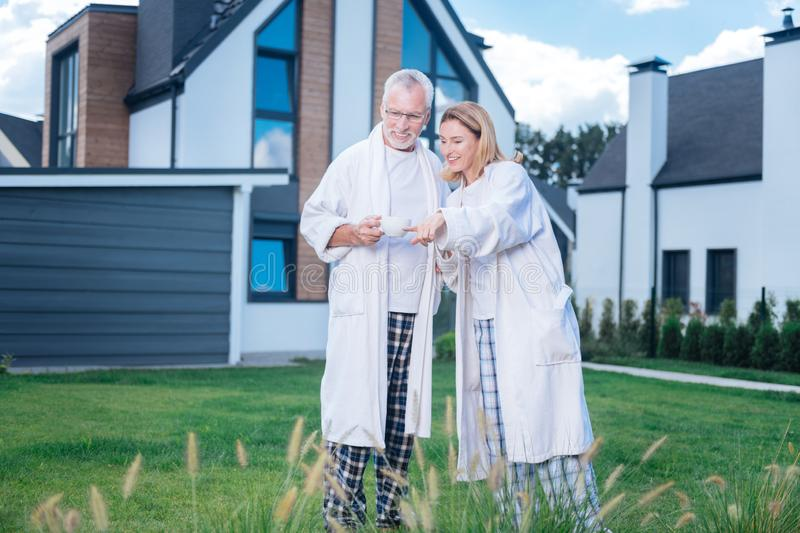 Couple of mature businessmen wearing bathrobes walking near their house stock images