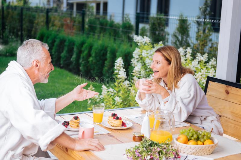 Couple of mature wife and husband enjoying their morning having tasty breakfast stock images