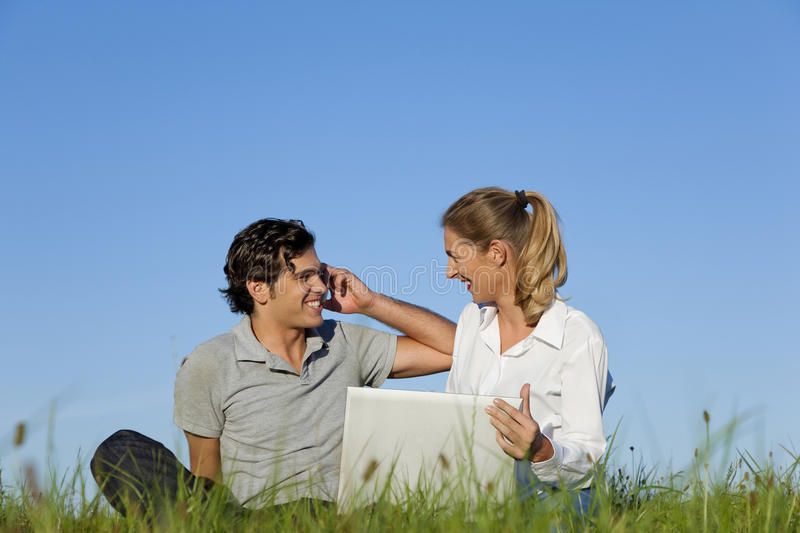 Download Couple On Meadow With Laptop And Mobile Phone Stock Image - Image: 15313875