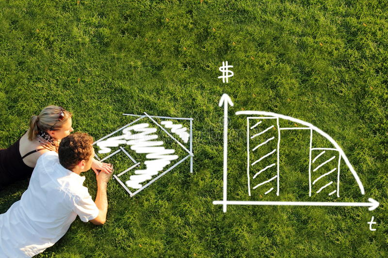 Couple in a meadow planning mortage for a house. A Couple in a meadow planning mortage for a house stock photo