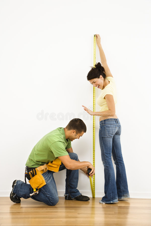 Couple measuring wall. royalty free stock image