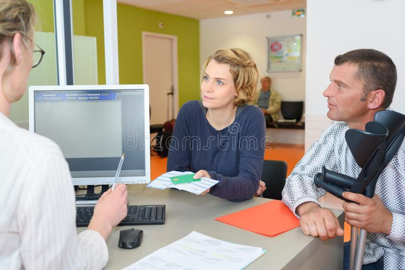 Couple with medical receptionist. Medical royalty free stock photos
