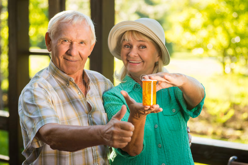 Couple with medicine bottle. Smiling elderly people. Effective pills against pain. Quality checked by patients royalty free stock photos