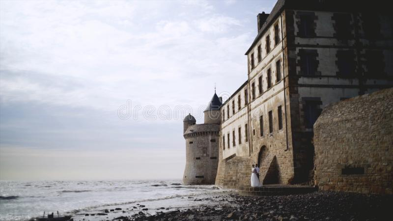 Couple of medieval coastal fortress. Action. Beautiful newlyweds stand at medieval stone fortress built on coast. Breathtaking scenery with medieval buildings stock images