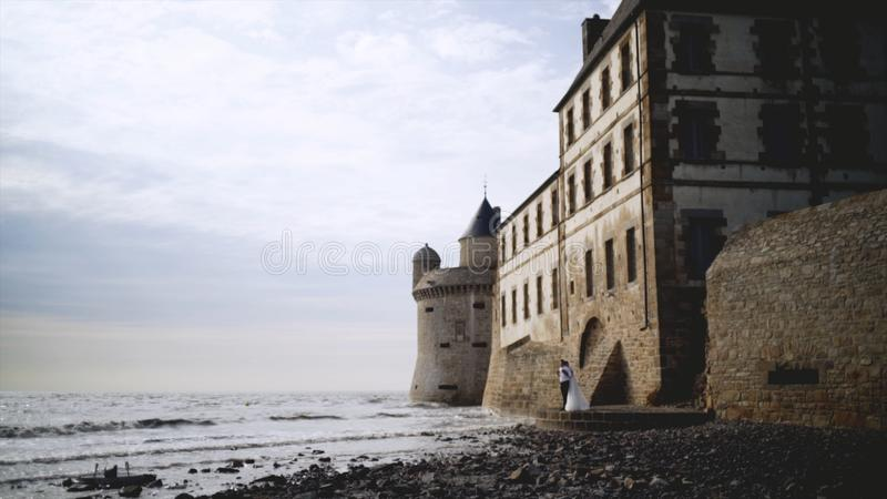 Couple of medieval coastal fortress. Action. Beautiful newlyweds stand at medieval stone fortress built on coast. Breathtaking scenery with medieval buildings royalty free stock photos