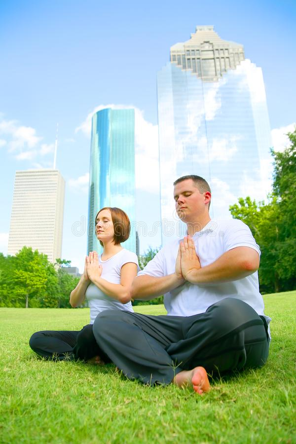Couple Meditating In Downtown stock photography