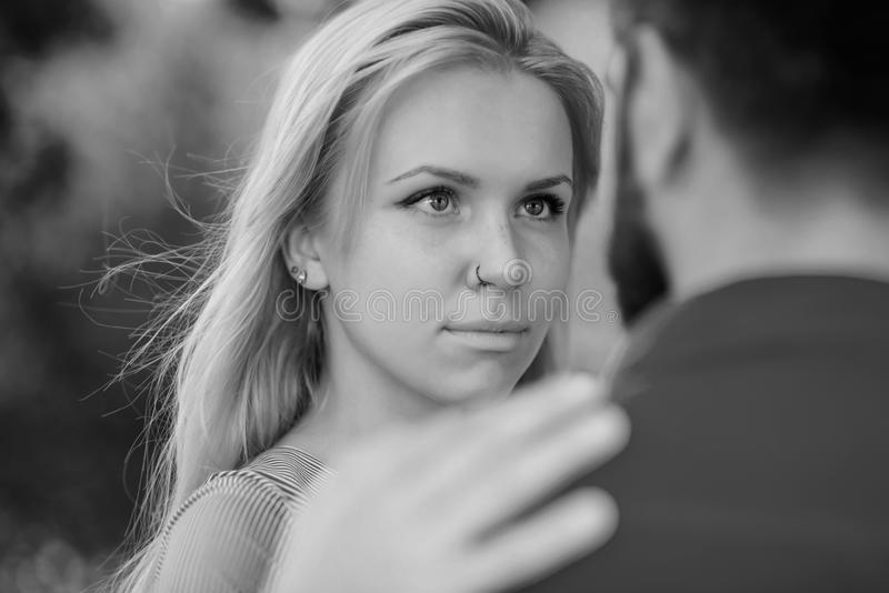 Couple meet on summer day, nature background, defocused, close up. Love, sympathy, dating, eye contact. Girl with calm. Face looks at bearded man, puts hand on stock images