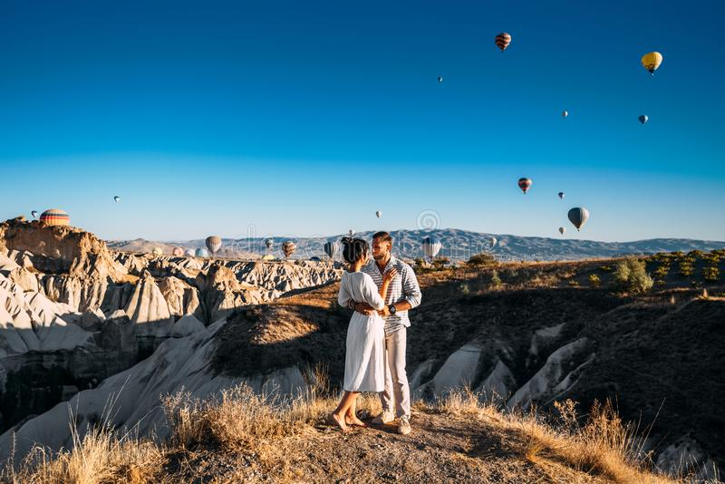 The couple meets the dawn. The man proposed to the girl. Family trip to Turkey. Couple at the balloon festival. Honeymoon trip. The couple meets the dawn. The stock photo