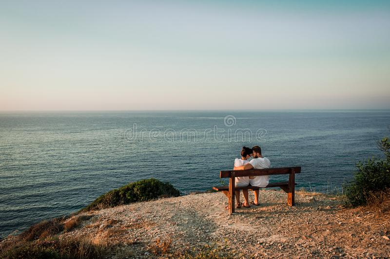 Couple in love at sunset. Man and woman at dawn. Couple sitting on a bench by the sea. Couple in love kissing by the sea. Man and woman traveling. Honeymoon royalty free stock photos