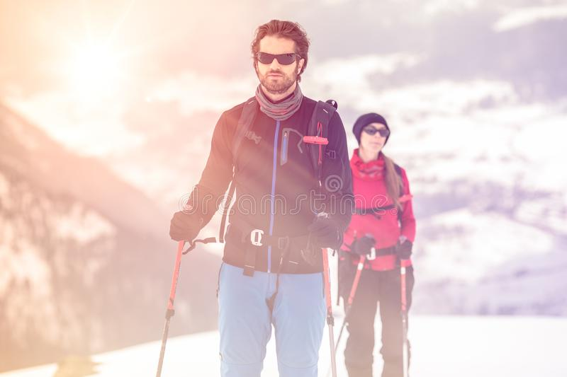 Couple man and woman skier exploring snowy land walking and skiing with alpine ski. Europe Alps. Winter sunny day, snow stock photos