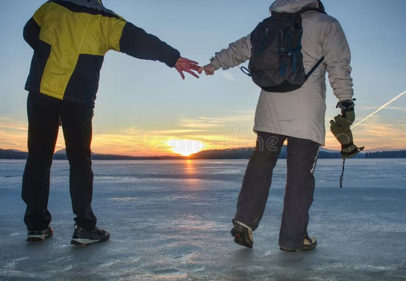 Couple, man and woman walking on ice on a frozen lake. Couple, men and women walking on the ice on a frozen lake. Happy couple on a frozen lake on a winter day stock image
