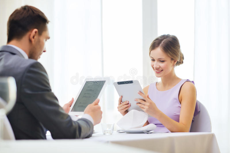 Couple with menus on tablet pc at restaurant stock photos