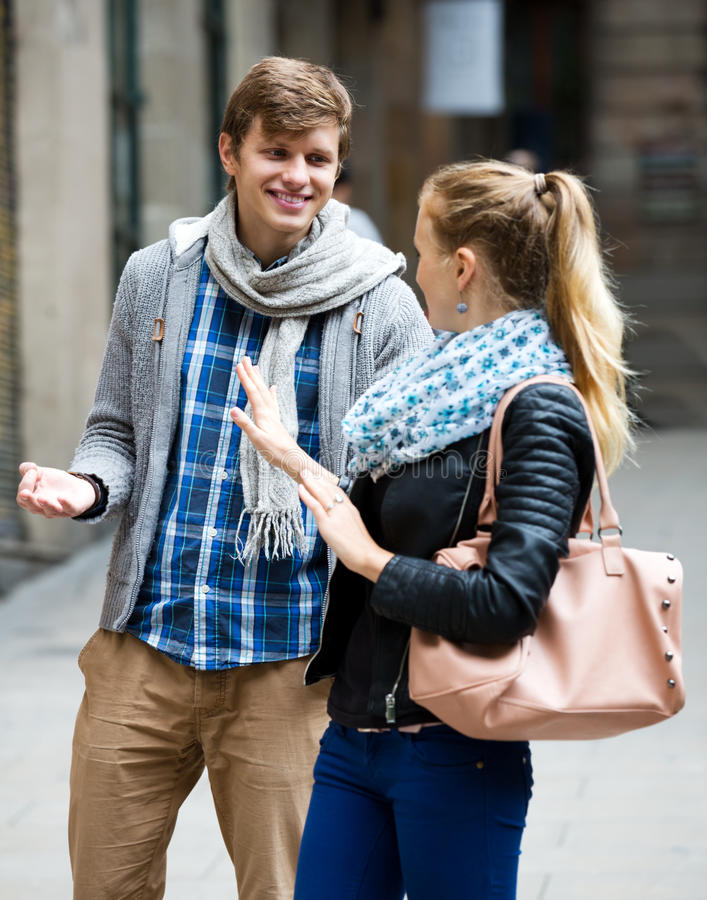 Couple met on the street. Blonde cannot get rid off bothering admirer outdoors stock photography