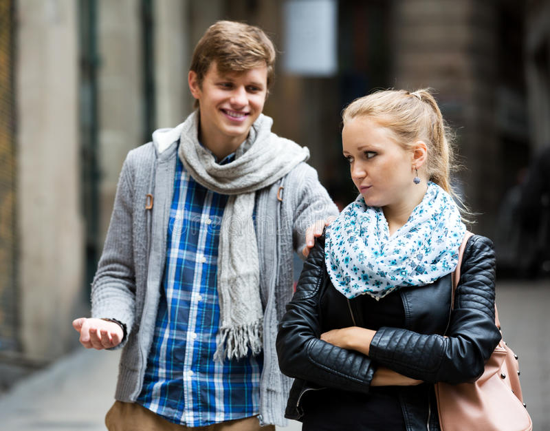 Couple met on the street. Sad blonde cannot get rid off bothering admirer outdoors. Focus on the woman stock photo