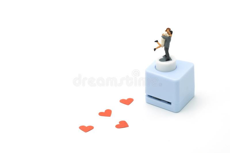 Couple Miniature 2 people standing with Heart shaped punching machine Punch red paper Red heart is the promise of love. as backgr stock photo