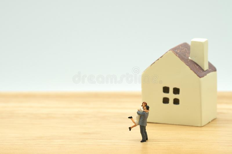 Couple Miniature 2 people standing model with house model make family Feel happy.as background real estate and family concept with stock images