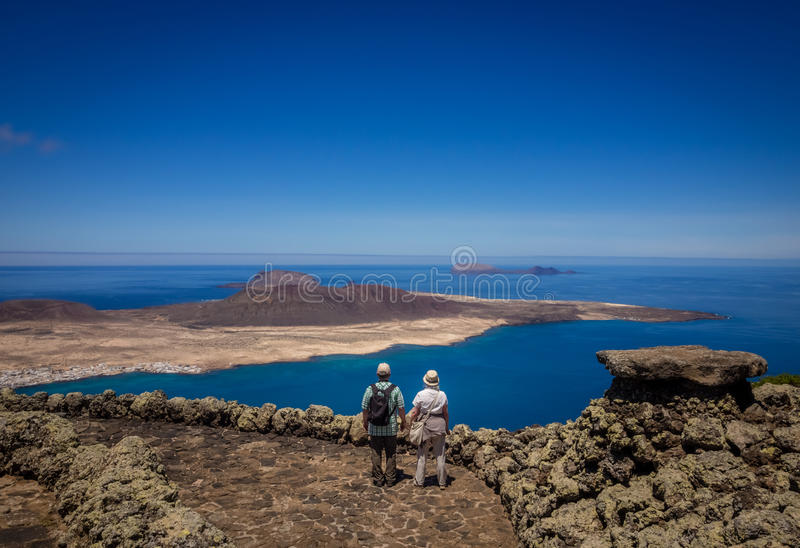 Couple on the Mirador del Rio. Couple of seniors admiring the view of the La Graciosa, Allegranza and Montana Clara islands as seen from the viewing platform of stock images