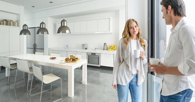 Couple in modern kitchen. Young couple drinking coffee in a modern kitchen stock images