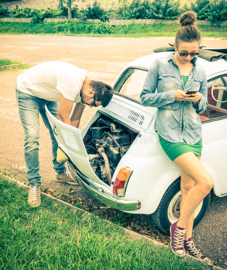Couple in a moment of troubles during a vintage classic car trip. Concept of modern relationship and interaction with new technologies - Problem solving and royalty free stock images