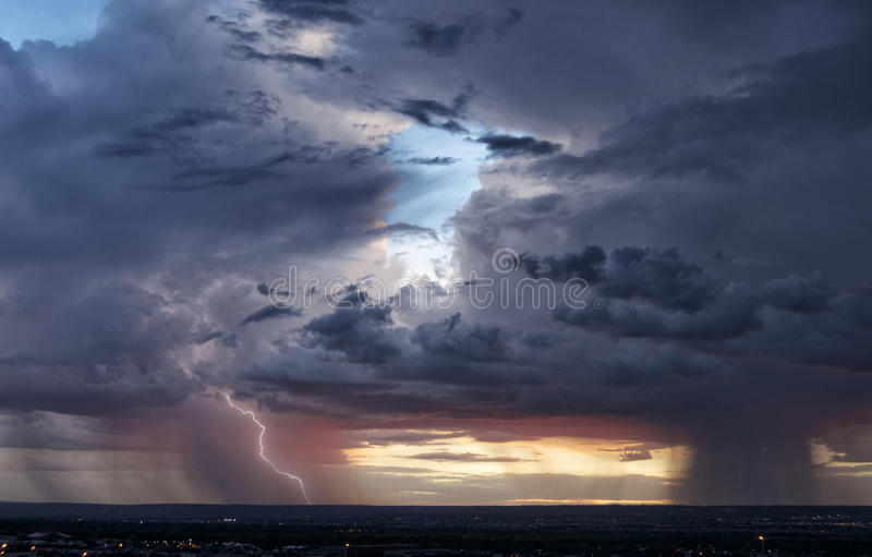 Couple of Monsoon Storms. Lightning and a vibrant sunset are displayed amidst two isolated monsoon thunderstorms. Image taken in Albuquerque, New Mexico stock photography
