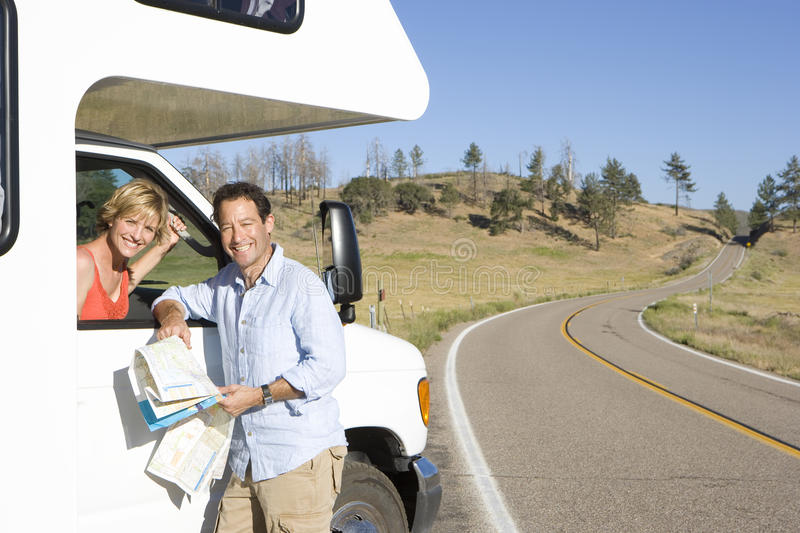 Couple with motor home, man with map, woman looking out of window, smiling, portrait stock image