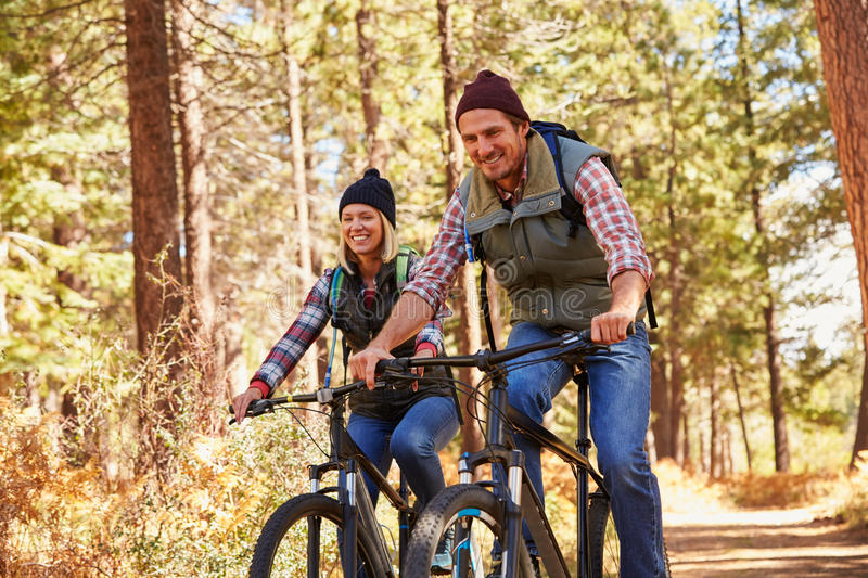 Couple mountain biking through forest, looking to camera royalty free stock image