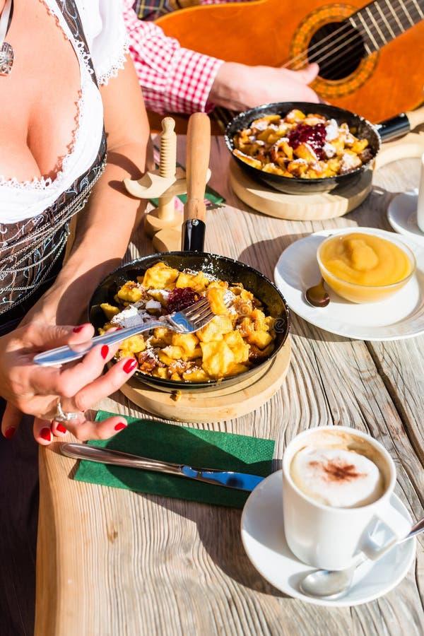Couple on mountain hut eating Kaiserschmarrn royalty free stock photos