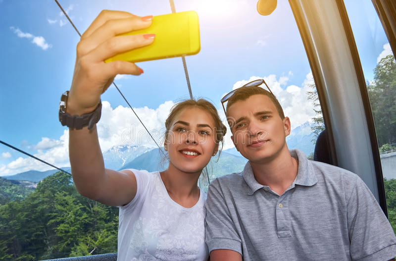 Couple on mountain lift taking a selfie on a sunny day royalty free stock photo