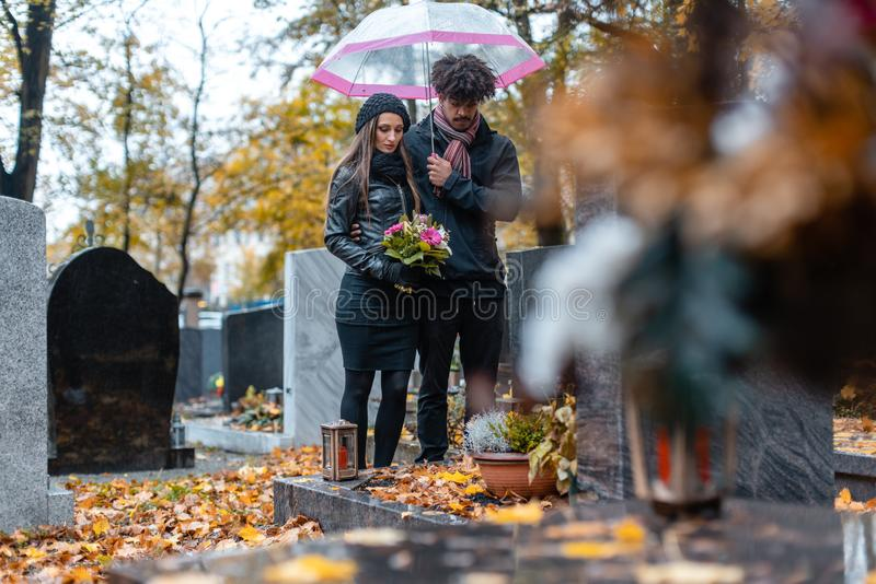 Couple mourning a deceased loved one on cemetery in fall stock photography