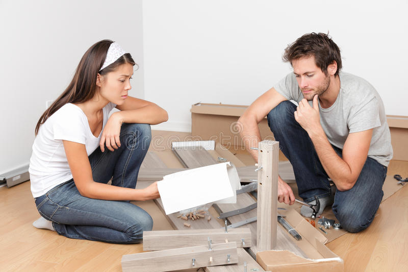 Couple moving in assembling bed furniture stock image