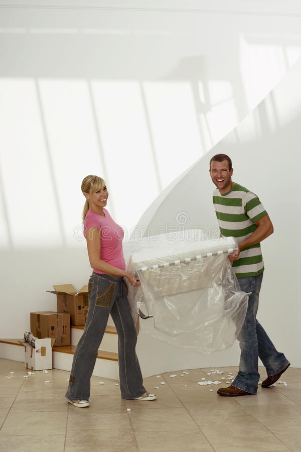 Couple moving house, carrying white chair wrapped in plastic sheet in room, smiling, portrait stock photography