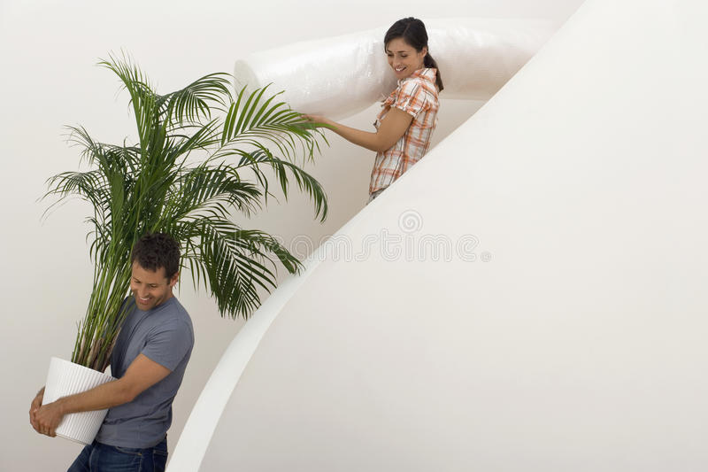 Couple moving house, man carrying large pot plant down staircase, woman carrying dust sheet, smiling royalty free stock photo