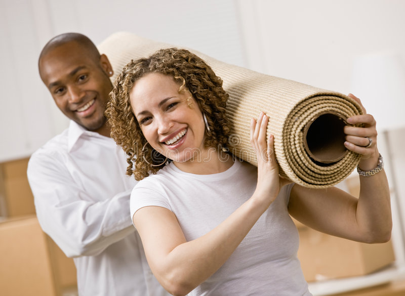 Couple moving into new home carrying rug royalty free stock photo