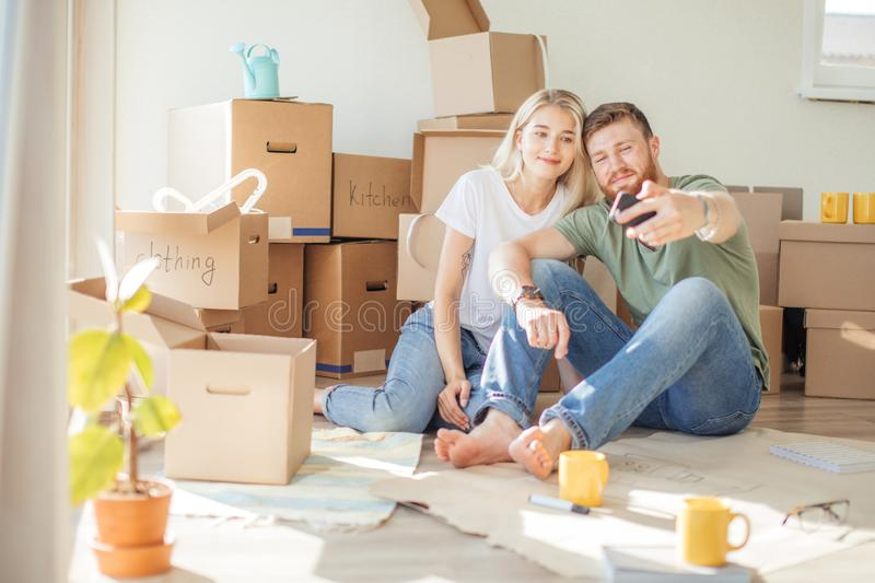 Couple moving in new home. Sitting on floor and relaxing after unpacking.Doing selfie with smartphone stock photos