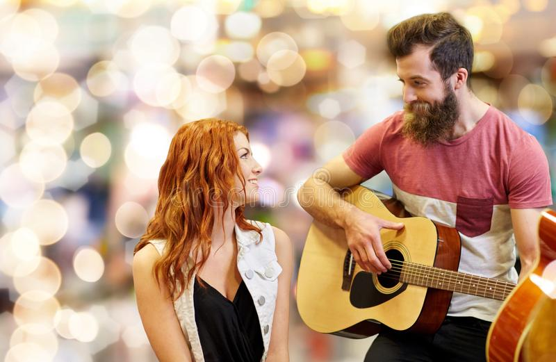 Couple of musicians playing guitar over lights. Music, people and entertainment concept - happy couple of musicians playing guitar over lights background stock photos