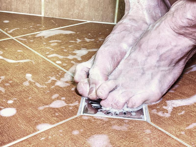 Couple of naked feet in shower. Detailed toes. Couple of naked feet in shower. Detailed foot toes, floor tilles, stainless sink. Feet washing in bathroom with royalty free stock photography