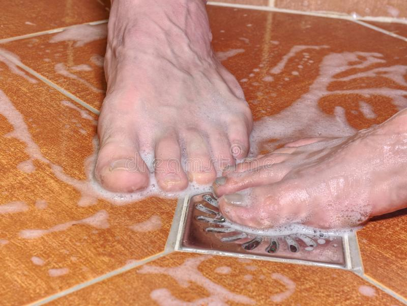 Couple of naked feet in shower. Detailed toes. Couple of naked feet in shower. Detailed foot toes, floor tilles, stainless sink. Feet washing in bathroom with royalty free stock images