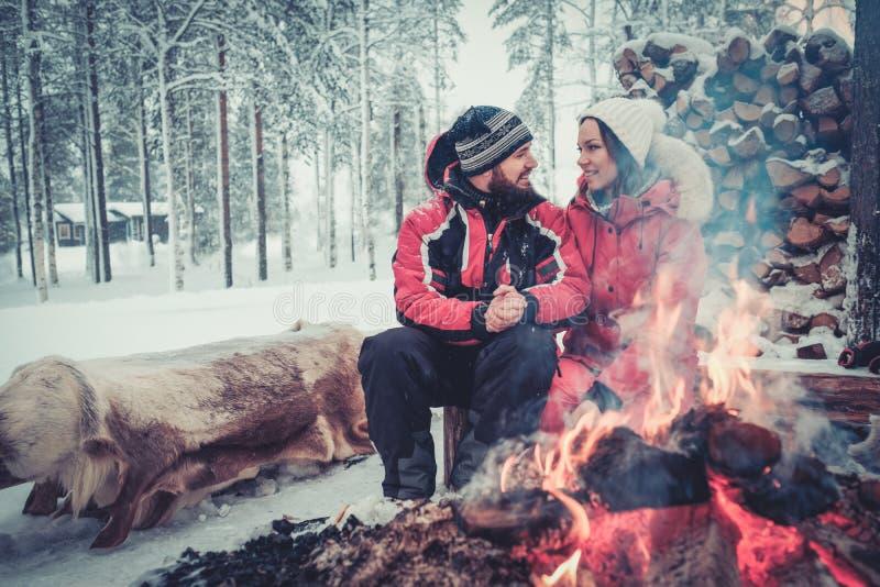 Couple near bonfire in winter landscape stock photo