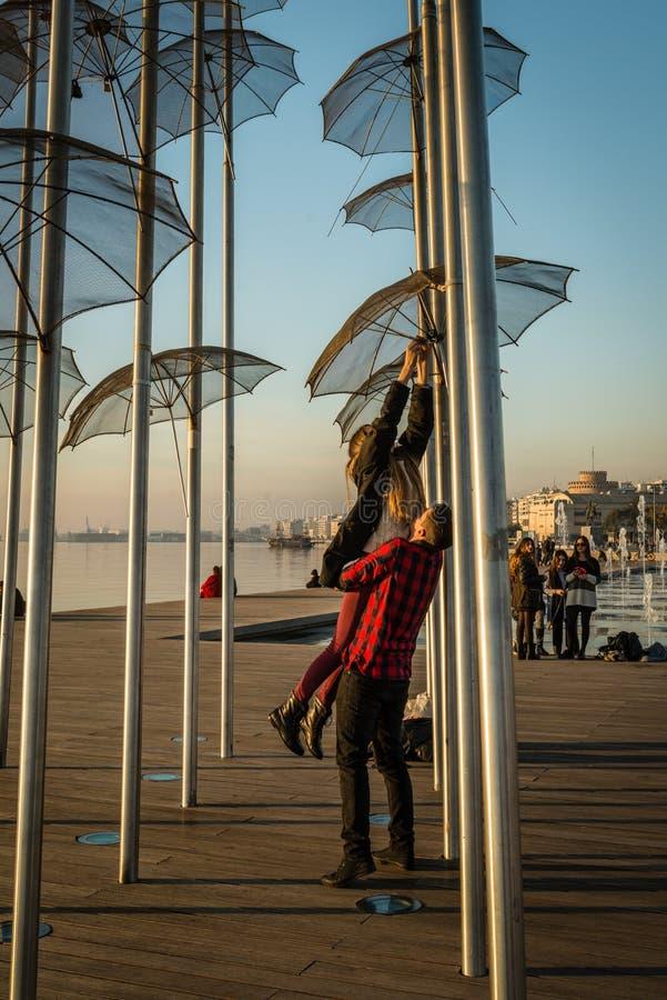 Couple near umbrellas in Thessaloniki. Thessaloniki, Greece - December 24, 2015: Couple is attaching padlocks on Umbrellas sculpture on Thessaloniki's sea stock photos