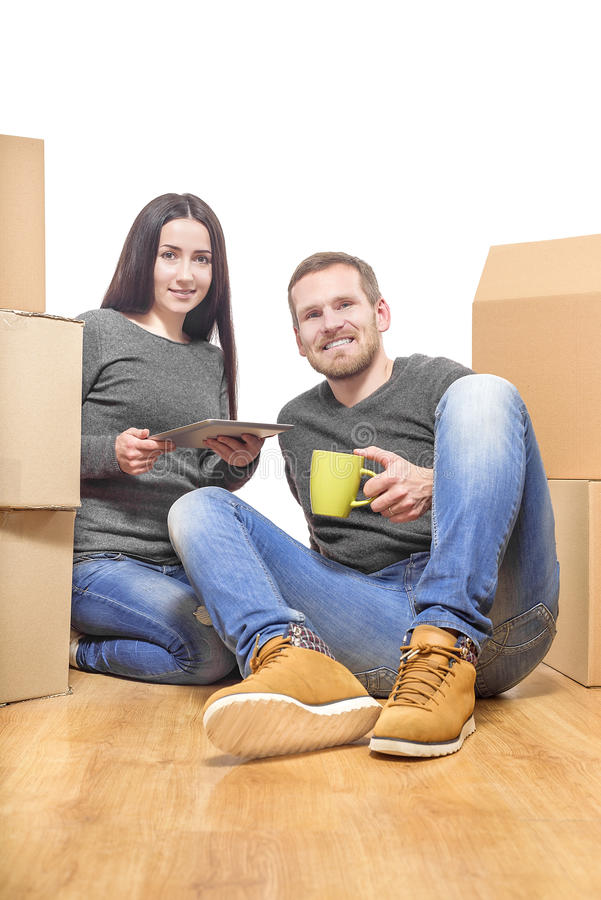 Couple in new home. Between the boxes, with a cup and Tablet PC in the hands royalty free stock photography