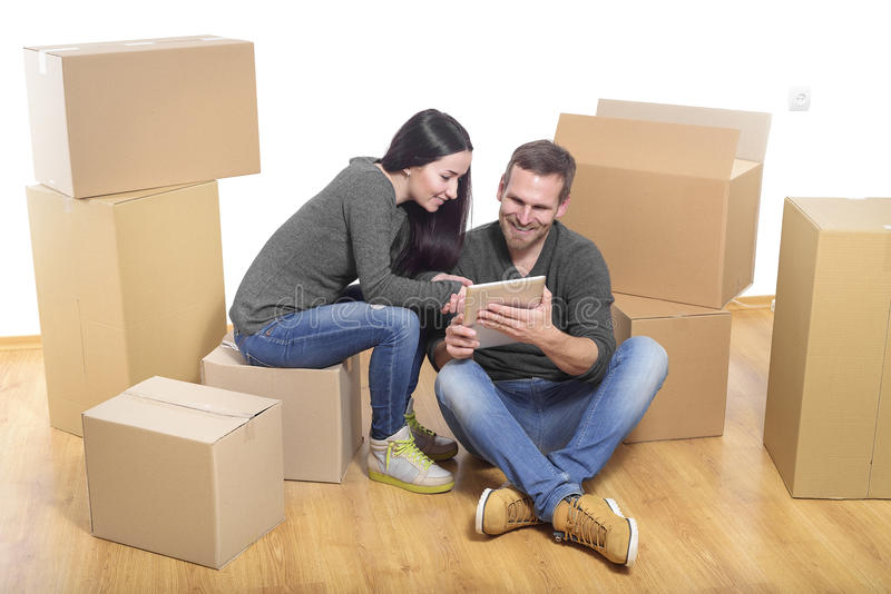 Couple in new home. Between the boxes, with a Tablet PC in the hands stock photo
